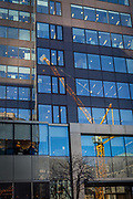 A construction crane reflected in the plate glass of office windows on Cannon Street in the City of London, on 22nd January 2019, in London England.