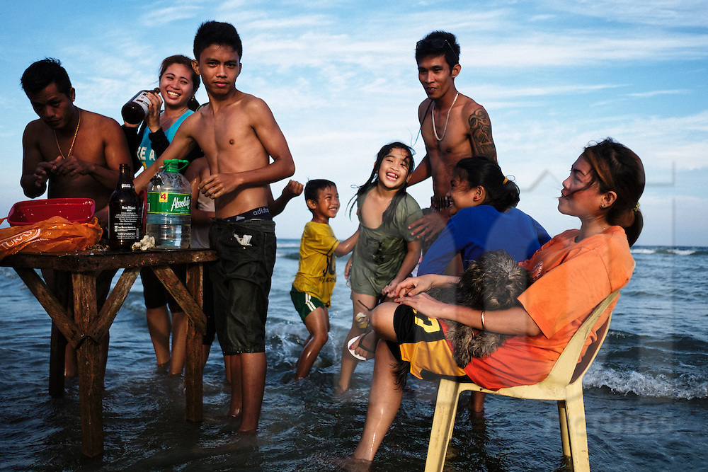 A Filipino family set a picnic in shallow waters, Central Visayas, Panglao Island, Philippines, Southeast Asia