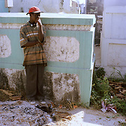 A Mourner at the main cemetery, Port Au Prince stands next to a pile of human remains. At the time of the earthquake, bodies were piling up in the streets and  Haitians were so desperate to deal with the cadavers that they would bring them to the cemetery and burn them where ever they could find space.