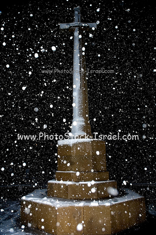 Israel, Jerusalem, Commonwealth World War I cemetery on Mt. Scopus, snow flakes falling on the entral memorial cross.