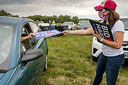 12 SEPTEMBER 2020 - DES MOINES, IOWA: CHRISTINA FREUNDLICH, with the Biden/Harris campaign, hands out Biden/Harris placards during the Polk County Democrats Steak Fry at Waterworks Park in Des Moines. The Steak Fry is the largest fundraiser of the year for Polk County Democrats. This year nearly 1,000 people attended. The Steak Fry observed public health guidelines. Normally the Steak Fry is a picnic but this year people stayed in their cars while meals were brought to them and they wore masks when they were outside of the cars. Most of the speakers appeared via online speeches.     PHOTO BY JACK KURTZ