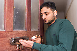 Husam demonstrates how he caught his finger in the letterbox. Amazon delivery driver Husam Aljuburi, 29, of Ealing, West London, lost the top quarter of his middle finger after tearing it off in a letterbox as he delivered a parcel at a home in Slough. London, April 09 2019.