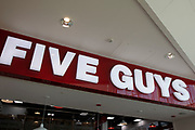 Sign for the food and burger restaurant brand Five Guys in Birmingham, United Kingdom.