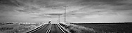 A loaded vehicle comes into view over a crest in the road in rural Klickitat County, WA, USA panorama(monochrome high contrast grainy image)