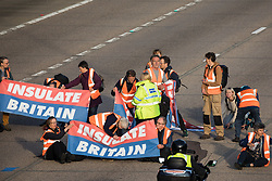 Ockham, UK. 21st September, 2021. Insulate Britain climate activists block the clockwise carriageway of the M25 between Junctions 9 and 10, some with paint, power tools and other implements, as part of a campaign intended to push the UK government to make significant legislative change to start lowering emissions. Both carriageways were briefly blocked before being cleared by Surrey Police.