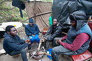 France. Refugees. Calais. So-called Jungle camp where Doctors of the World have a clinic. Sudanese refugees try to keep warm