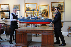 Bonham's Managing Director Charles Graham-Campbell and head of the sale Kenneth Naples inspect a mid 20th century model of Russian battleship 'Admiral Oushavov' which is up for sale in the nautical collection auction at Bonham's in Edinburgh on November 15th.<br /> <br /> © Dave Johnston/ EEm