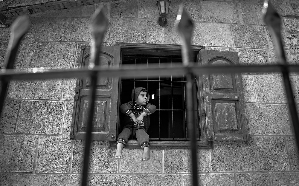 A boy looks out from a window in Byblos, Lebanon.