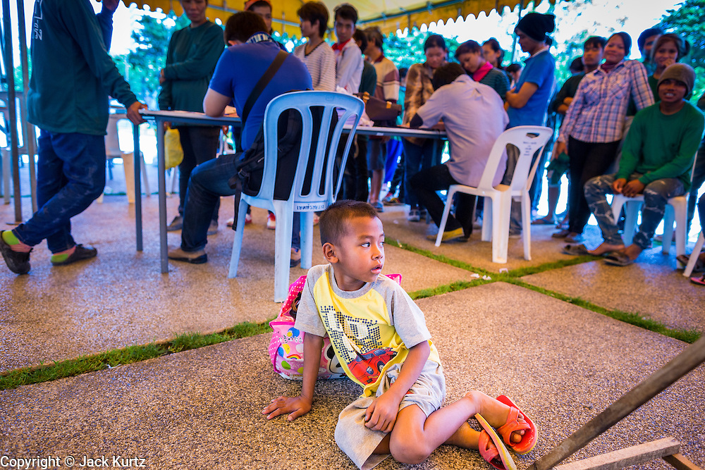"""17 JULY 2014 - BANGKOK, THAILAND: A Cambodian child waits for his parents to finish registering for temporary Thai ID cards at the temporary """"one stop service center"""" in the Bangkok Youth Center in central Bangkok. Thai immigration officials have opened several temporary """"one stop service centers"""" in Bangkok to register undocumented immigrants and issue them temporary ID cards and work permits. The temporary centers will be open until August 14.    PHOTO BY JACK KURTZ"""