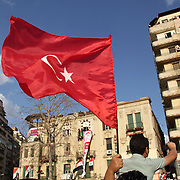 In solidarity with his fellow revolutionaries, an Egyptian man raises a Tunisian flag in Cairo's Tahrir Square.