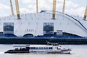An Uber Boat on the river Thames passes the O2 Arena (formerly the Millennium Dome) on the Greenwich Peninsula, beneath a blue sky and clouds, on 11th August 2021, in London, England. The O2 is a music, sport and entertainment venue, opened in the year 2000.