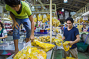 19 OCTOBER 2012 - BANGKOK, THAILAND: Men stock their booth with marigold garlands in the Bangkok Flower Market. The Bangkok Flower Market (Pak Klong Talad) is the biggest wholesale and retail fresh flower market in Bangkok.  The market is busiest between 3:30AM and 6AM. Thais grow and use a lot of flowers. Some, like marigolds and lotus, are used for religious purposes. Others are purely ornamental.        PHOTO BY JACK KURTZ