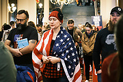 "11 JANUARY 2021 - DES MOINES, IOWA: A woman draped in an American flag prays in the Rotunda of the Iowa State Capitol in Des Moines. Hundreds of Iowans, from across the state, came to the State Capitol to protest the Governor's COVID-19 mitigation efforts. The Coronavirus (SARS-CoV-2) mitigation guidelines include a mask mandate indoors when it isn't possible to social distance. But the Governor specifically exempted the State Capitol. No one in the crowd wore a mask and there was no effort to follow ""social distancing"" guidelines. There were also ""anti-Vaxxers"" in the crowd who protested the vaccine efforts and said vaccines were unsafe.           PHOTO BY JACK KURTZ"
