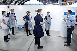 © Licensed to London News Pictures. 13/04/2020. Manchester, UK. Nursing staff on Ward 7 put on their PPE and are given final advice ahead of the hospital's official opening on Friday 17th April 2020 . The National Health Service has built a 648 bed field hospital for the treatment of Covid-19 patients , at the historical railway station terminus which now forms the main hall of the Manchester Central Convention Centre . The facility is due to open this week (commencing Easter Monday , 13th April 2020 ) and will treat patients from across the North West of England , providing them with general medical care and oxygen therapy after discharge from Intensive Care Units . Photo credit: Joel Goodman/LNP