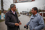 Roma activist Gheorghe Tudor with Gheorghe Costoiu - one of the six elected local Roma councilors at the Saturday morning market place in Marginenii de Jos.
