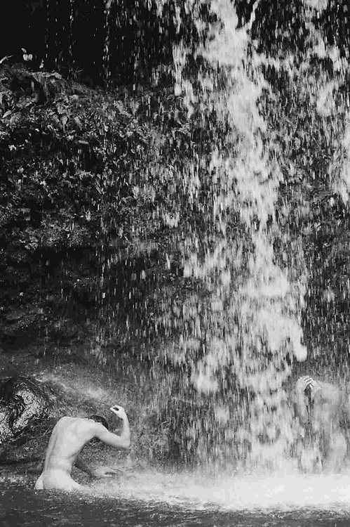 two nude men under a waterfall in Maui, Hawaii