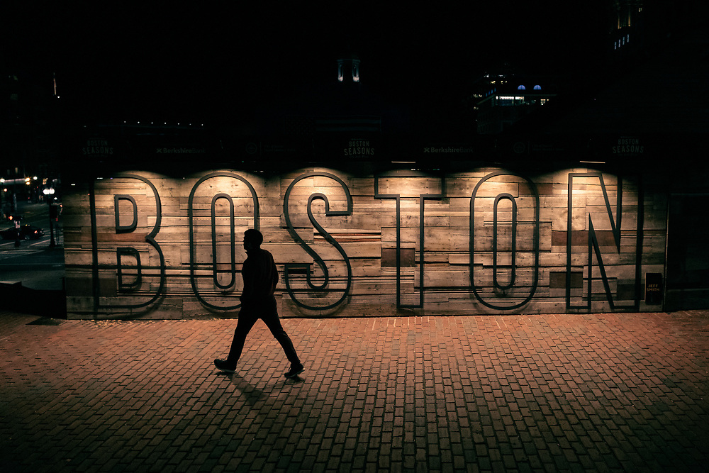 A pedestrian walking past the Boston sign at City Hall Plaza on a cold autumn evening.