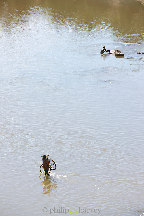 Man crossing river with his bicycle at Amboasary Sud, near the Berenty Reserve, Madagascar