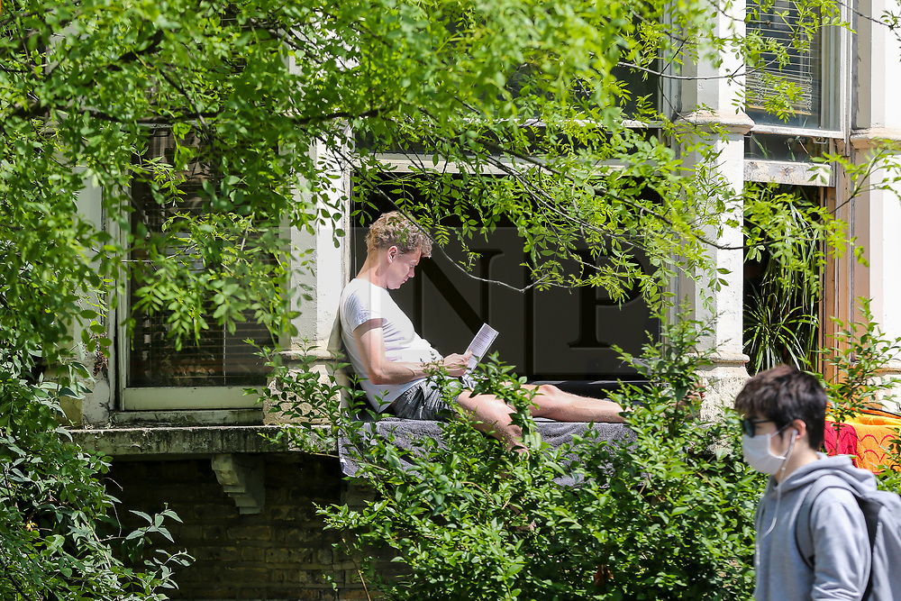 © Licensed to London News Pictures. 09/05/2020. London, UK. A man sitting on a window seal in a north London house takes advantage of the sunny and warm weather, on what could be he hottest day of the year so far. Prime Minister Boris Johnson is set to announce on Sunday, 10 May, measures to ease coronavirus lockdown, which was introduced on 23 March to slow the spread of the COVID-19. Photo credit: Dinendra Haria/LNP