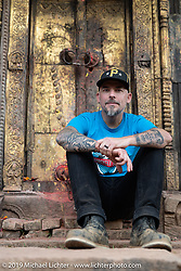 Devil Chicken artist Chris Galley outside a temple in Nuwakot during Motorcycle Sherpa's Ride to the Heavens motorcycle adventure in the Himalayas of Nepal. This first day of riding took us from Kathmandu to Nuwakot. Monday, November 4, 2019. Photography ©2019 Michael Lichter.