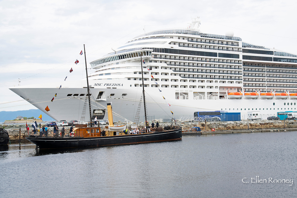 An old steam powered boat next to a huge modern cruise ship in the harbour in  Trondheim, Trondelag, Norway, Europe