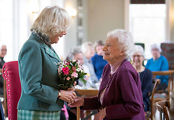 The Duchess of Cornwall, known as the Duchess of Rothesay in Scotland, is presented with flowers by Zan Grant, 91 from Braemar, during her visit to the Duke of Rothesay Highland Games Pavilion in Braemar, Aberdeenshire.