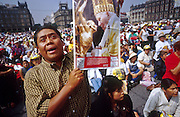 """jku032303056 - 31 JULY 2002 - MEXICO CITY, DF, MEXICO: People pray on the Zocalo in the historic center of Mexico City during a Papal mass televised to the Zocalo on large screen """"jumbotron"""" televisions. The mass, led by Pope John Paul II, was at the Basilica of Guadalupe in Mexico City, July 31, 2002. The Pontiff, making his fifth trip to Mexico, canonized Juan Diego, the Mexican Indian who first saw the image of the Virgin of Guadalupe in 1531. Juan Diego is now known at Saint Juan Diego. PHOTO © JACK KURTZ  RELIGION  INDIGENOUS  CULTURE  PATRIOTISM"""
