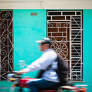 Motorbike passing a colourful facade in Cienfuegos