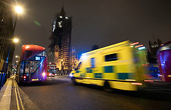 © Licensed to London News Pictures. 31/12/2020. London, UK. An ambulance races to to Thomas' Hospital past Parliament ahead of midnight and a muted New Year's Eve in central London. Photo credit: Peter Macdiarmid/LNP