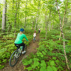 A woman and her kids ride mountain bikes on a trail near Deboullie Pond in Aroostook County, Maine. Deboullie Public Reserve Land.