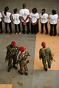 """Soldiers stand guard by a group of students during the visit of Guinea's president Captain Moussa Dadis Camara at the Kofi Annan private university in Conakry, Guinea on Thursday March 5, 2009. Camara, who took power after a coup in December 2008, was visiting the university to """"meet the youth"""", as part of his efforts to solidify his support from Guinea's population.(Olivier Asselin for the New York Times)"""