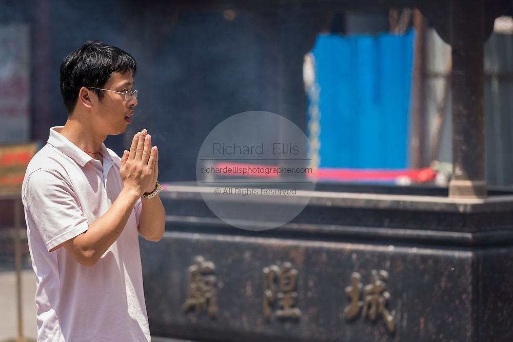 A man prays at Chenghuang Miao or City God Temple in Yu Yuan Gardens bazaar Shanghai, China