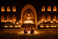 BAGAN, MYANMAR - CIRCA DECEMBER 2017: Monks seating around candelights on a temple in Bagan