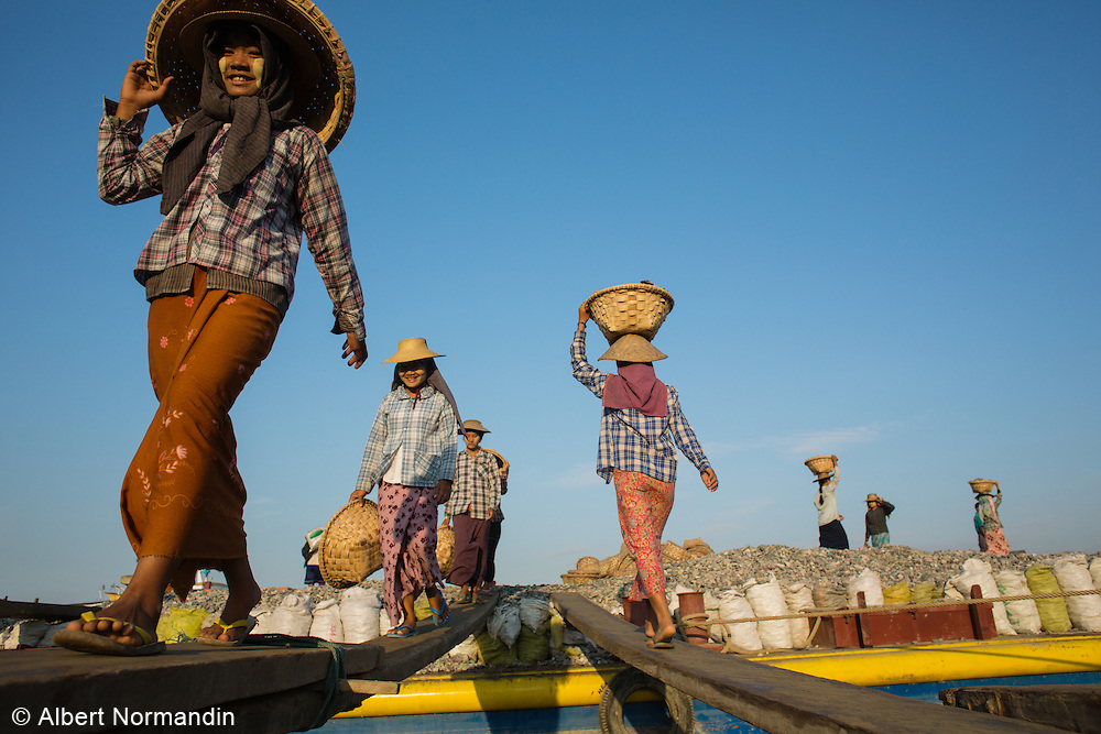 Young girls carry rocks, gravel in baskets loading a boat, walking on planks, Mandalay