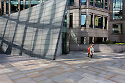 1980s architecture at the Broadgate City of London development and stooping woman.