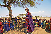 Maasai teacher instructing children in rural tribal village near the Olduvai Gorge