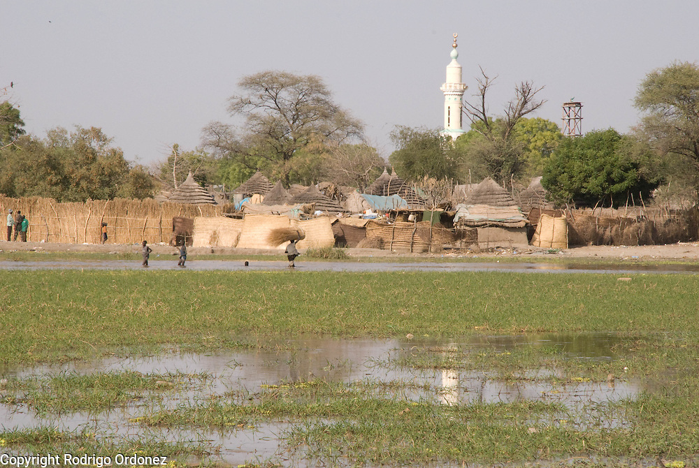 Water covers the back streets of the town of Abyei, near the grass market.
