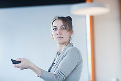 Mature woman holding a mobile phone in lecture hall, Freiburg Im Breisgau, Baden-Württemberg, Germany