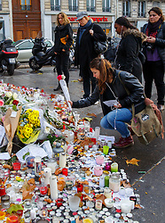 © Licensed to London News Pictures. 17/11/2015. Paris, France. Mourners visit a memorial outside Bataclan cafe in Paris, France following the Paris terror attacks on Tuesday, 17 November 2015. Photo credit: Tolga Akmen/LNP