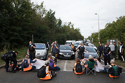Godstone, UK. 13th September, 2021. Surrey Police officers start to move climate activists from Insulate Britain blocking a slip road from the M25, causing long tailbacks on the motorway, as part of a new campaign intended to push the UK government to make significant legislative change to start lowering emissions. The activists, who wrote to Prime Minister Boris Johnson on 13th August, are demanding that the government immediately promises both to fully fund and ensure the insulation of all social housing in Britain by 2025 and to produce within four months a legally binding national plan to fully fund and ensure the full low-energy and low-carbon whole-house retrofit, with no externalised costs, of all homes in Britain by 2030 as part of a just transition to full decarbonisation of all parts of society and the economy.