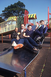 Multiracial group of youths sliding down slide in children's playground,