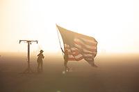 Burner holding large American flag.