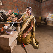 INDIVIDUAL(S) PHOTOGRAPHED: Sonali Tulpule. LOCATION: Ahirwade, Maharashtra, India. CAPTION: Sonali cooks the family meal on a small cookstove, which is powered by biogas from her family's recently installed biogas unit. This simple technology ferments organic waste and turns it into methane gas, giving the family access to a clean and renewable source of energy, meaning that they no longer need to rely on firewood, which they have to gather, or large gas canisters, which are challenging to transport.