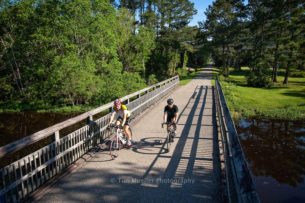 Bicyclist Tracy Johnson, left, and Ralph Tortorich ride the Tammany Trace Trail just south of Koop Drive in St. Tammany Parish, Louisiana.