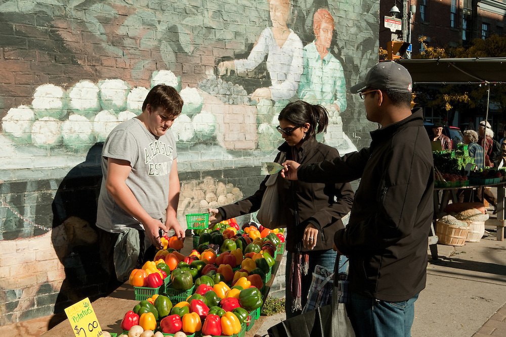 A couple buys some bell peppers at at outdoor stall at Toronto's St. Lawrence farmers' market.