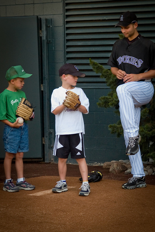 TAYLOR BUCHHOLZ, pitcher for the Colorado Rockies, gives seven year-old ALEX URBACH PITCHINGS TIPS.