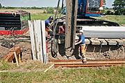 Nederland, Wolveren, 26-5-2020  Delen van de Waaldijk worden komende jaren versterkt. Naast het verhogen en stabiliseren van de dijk zullen er ook damwanden geplaatst worden, die zogeheten piping voorkomen, het wegspoelen door onergrondse waterlopen van zand onder en achter de dijk . Bij wijze van proef plaatst het waterschap rivierenland lange kunststof damwanden. Deze zijn duurzamer en goedkoper, maar zwakker dan de gebruikelijke stalen wanden. De proef moet inzicht geven in het werken met dit type damwanden in een harde ondergrond.     Het werk vandaag kende wat vertraging omdat een accu was gestolen en de damwand de laatste twee meter niet verder ging vanwege een harde zandlaag.Foto: Flip Franssen
