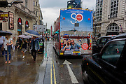 The southern French city of Marseille appears as an advert on the rear of a London tour bus travelling through the capital's streets, through a wet Piccadilly Circus.
