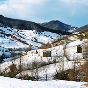 Winter agricultural landscape close by to the village of Botiza, Maramures, Romania. In the Romanian Carpathians, the agricultural landscape consists of a diverse mixture of small fields, meadows and orchards situated around villages, interspersed with forest and woodlands.