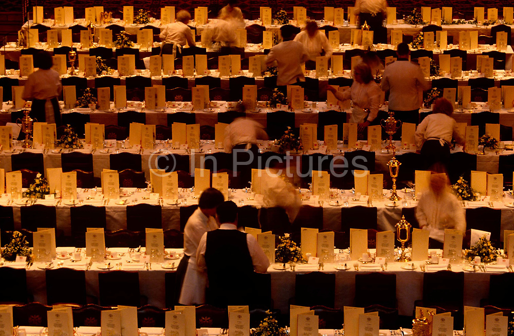 Catering staff polish silverware and glasses at the tables soon to be occupied by City of London dignitaries at the Guildhall when the Rt. Hon. Kenneth Clarke MP, the then-Chancellor in John Major's Conservative government of makes his annual speech. Tables and cutlery are prepared before the bankers and financiers file in for this formal banquet in the ancient City's town hall. The Banker's Dinner is held every in June when the Chancellor of the Exchequer delivers a speech known as the Mansion House Speech hosted by the Lord Mayor of London when the Chancellor delivers his forecast predicts growth and prosperity.